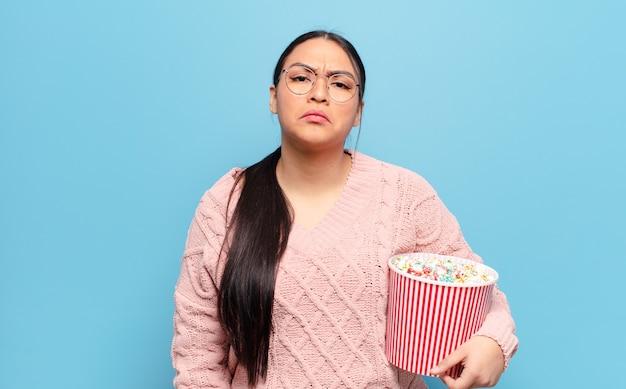Hispanische frau, die traurig und weinerlich mit einem unglücklichen blick fühlt und mit einer negativen und frustrierten haltung weint