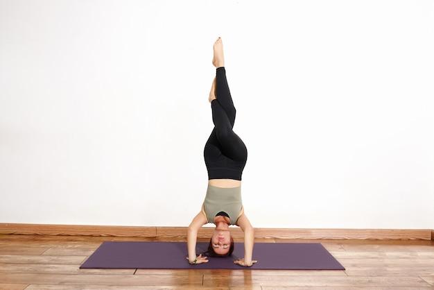 Hispanische frau, die yoga-posen durchführt