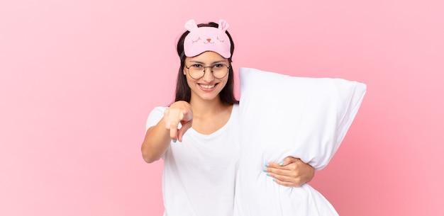 Hispanische frau im pyjama, die auf die kamera zeigt, die sie auswählt und ein kissen hält