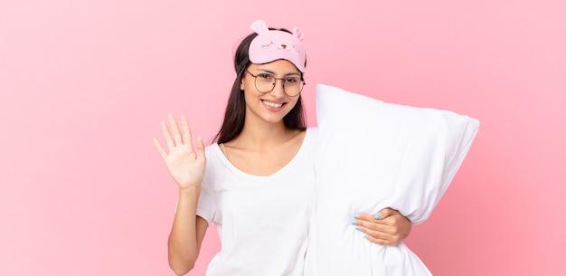 Hispanische frau im pyjama, die glücklich lächelt, mit der hand winkt, sie begrüßt und begrüßt und ein kissen hält