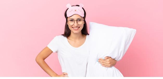Hispanische frau im pyjama, die glücklich mit einer hand auf der hüfte lächelt und selbstbewusst ist und ein kissen hält