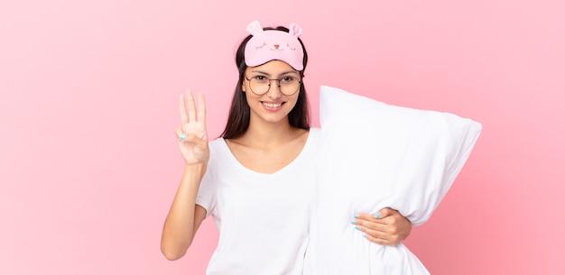 Hispanische frau im pyjama, die lächelt und freundlich aussieht, die nummer drei zeigt und ein kissen hält