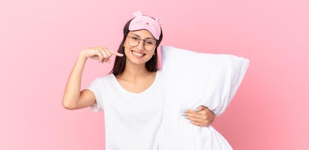 Hispanische frau im pyjama, die selbstbewusst auf ihr breites lächeln zeigt und ein kissen hält
