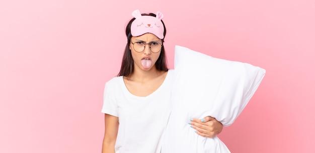 Hispanische frau im pyjama, die sich angewidert und gereizt fühlt und die zunge herausstreckt und ein kissen hält