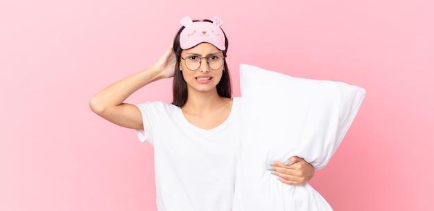 Hispanische frau im schlafanzug, die sich gestresst, ängstlich oder ängstlich fühlt, die hände auf dem kopf hat und ein kissen hält