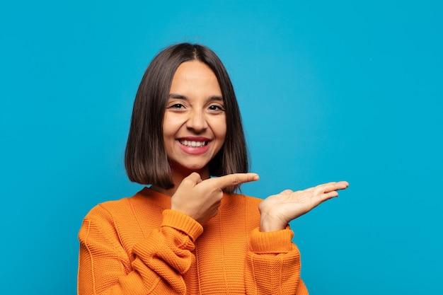 Hispanische frau lächelt, fühlt sich glücklich, sorglos und zufrieden, zeigt auf konzept oder idee auf kopienraum auf der seite