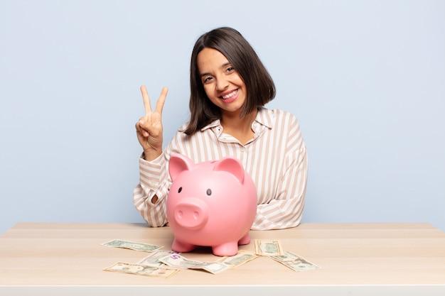 Hispanische frau lächelt und sieht freundlich aus und zeigt nummer zwei mit einem sparschwein