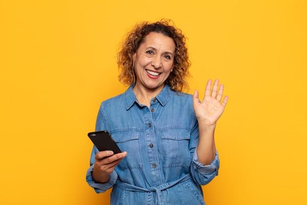 Hispanische frau mittleren alters, die glücklich und fröhlich lächelt, hand winkt, sie begrüßt und begrüßt oder sich verabschiedet