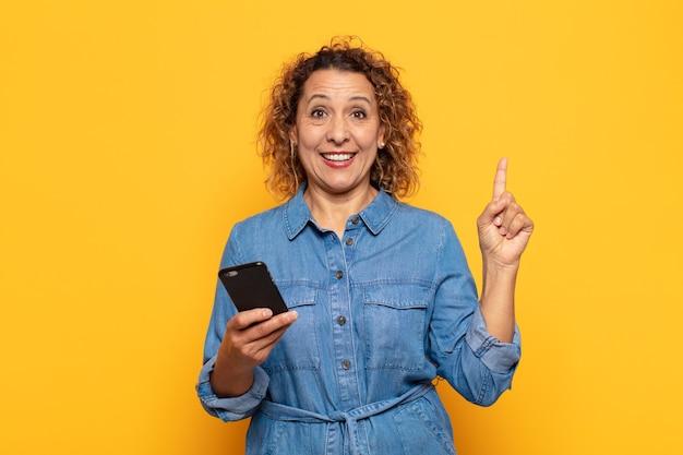 Hispanische frau mittleren alters, die sich wie ein glückliches und aufgeregtes genie fühlt, nachdem sie eine idee verwirklicht hat, fröhlich den finger hebt, heureka!