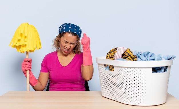Hispanische frau mittleren alters, die unglücklich und gestresst schaut, selbstmordgeste, die waffenzeichen mit hand macht, zeigt auf kopf