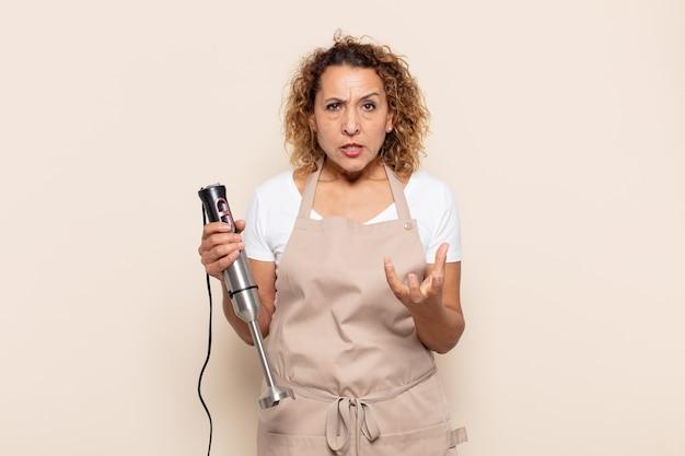 Hispanische frau mittleren alters, die wütend, genervt und frustriert aussieht und wtf schreit oder was mit ihnen los ist