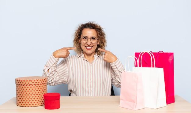 Hispanische frau mittleren alters, die zuversichtlich lächelt und auf eigenes breites lächeln zeigt, positive, entspannte, zufriedene haltung