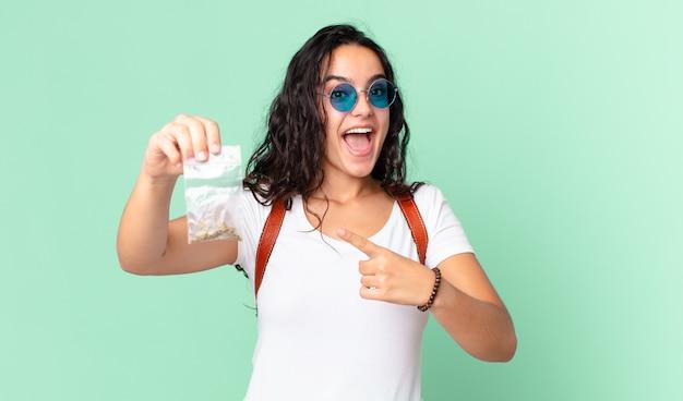 Hispanische hübsche frau, die aufgeregt und überrascht aussieht, die auf die seite zeigt und eine marihuana-tasche hält