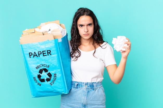 Hispanische hübsche frau, die eine recyclingpapiertüte hält