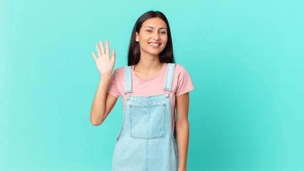 Hispanische hübsche frau, die glücklich lächelt, die hand winkt, sie begrüßt und begrüßt