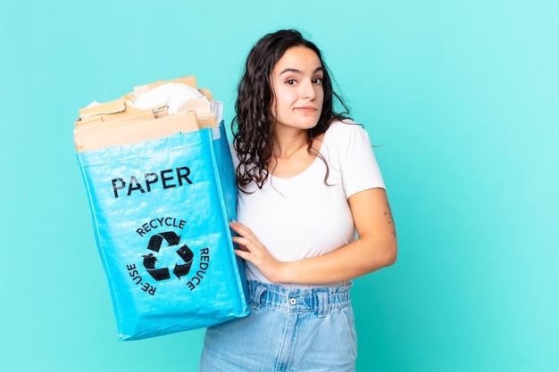 Hispanische hübsche frau, die mit den schultern zuckt, sich verwirrt und unsicher fühlt und eine recyclingpapiertüte hält