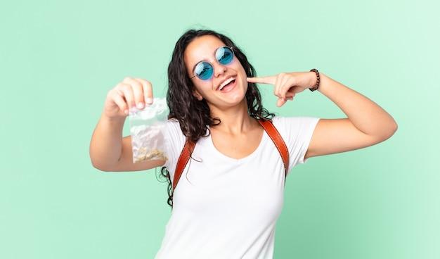 Hispanische hübsche frau, die selbstbewusst auf ihr eigenes breites lächeln lächelt und eine marihuana-tasche hält