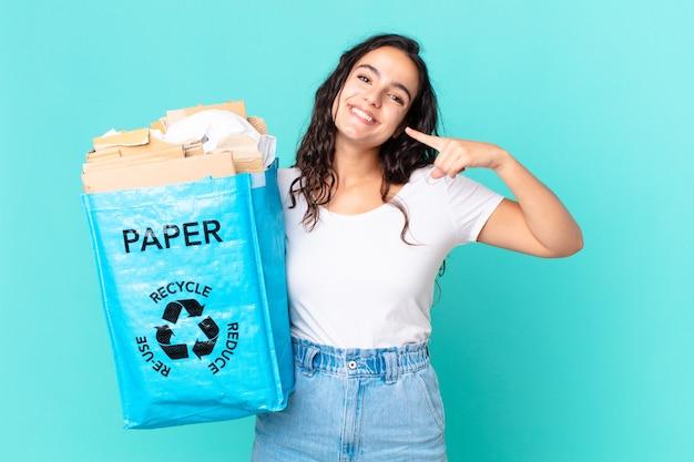 Hispanische hübsche frau, die selbstbewusst auf ihr eigenes breites lächeln lächelt und eine recyclingpapiertüte hält