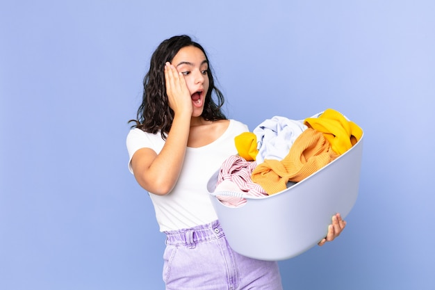 Hispanische hübsche frau, die sich glücklich, aufgeregt und überrascht fühlt und einen wäschekorb hält