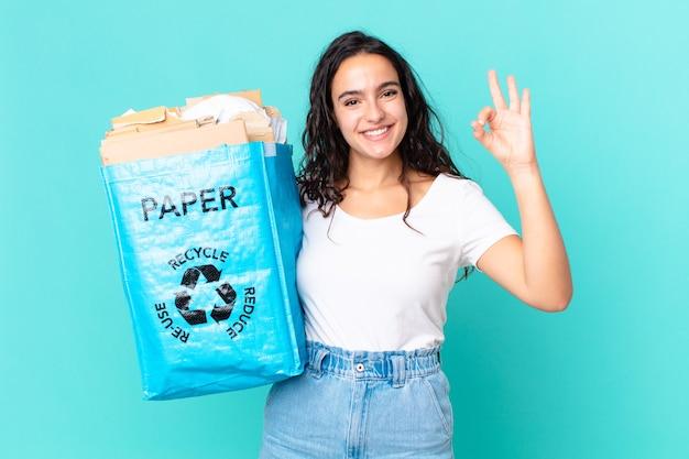 Hispanische hübsche frau, die sich glücklich fühlt, zustimmung mit einer okayen geste zeigt und eine recyclingpapiertüte hält