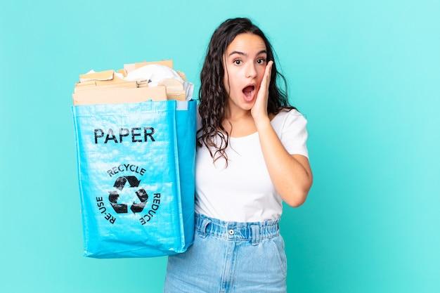 Hispanische hübsche frau, die sich schockiert und verängstigt fühlt und eine recyclingpapiertüte hält