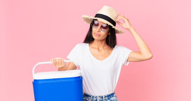 Hispanische hübsche frau, die sich verwirrt und verwirrt fühlt und sich den kopf mit einem tragbaren picknickkühlschrank kratzt