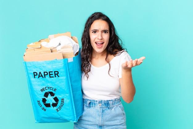 Hispanische hübsche frau, die verzweifelt, frustriert und gestresst aussieht und eine recyclingpapiertüte hält