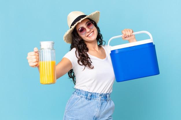 Hispanische hübsche frau mit einem tragbaren kühlschrank und einem orangensaft