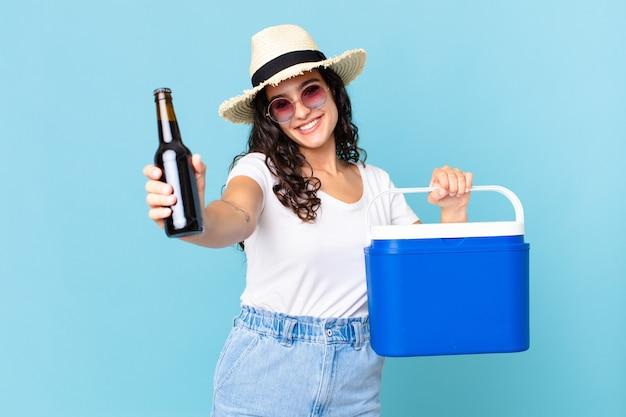 Hispanische hübsche frau mit einem tragbaren kühlschrank und einer bierflasche