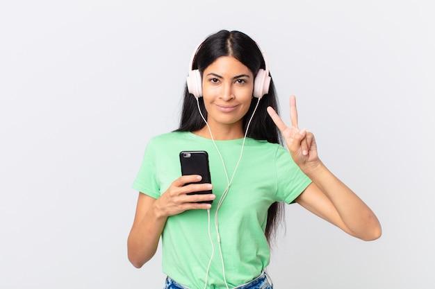 Hispanische hübsche frau mit kopfhörern und einem smarphone