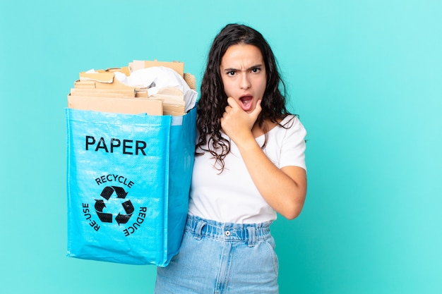 Hispanische hübsche frau mit weit geöffnetem mund und augen und hand am kinn und hält eine recyclingpapiertüte