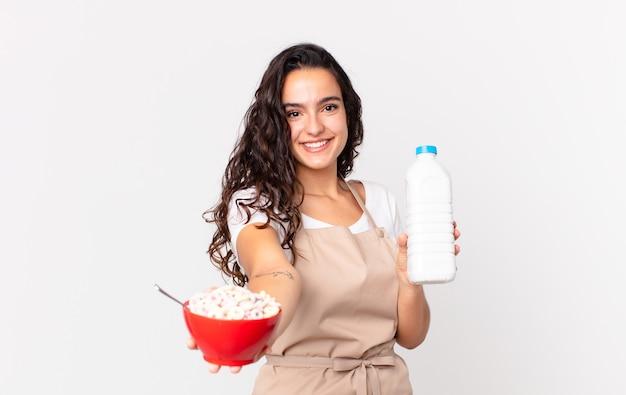 Hispanische hübsche kochfrau, die eine frühstücksschüssel mit milch hält