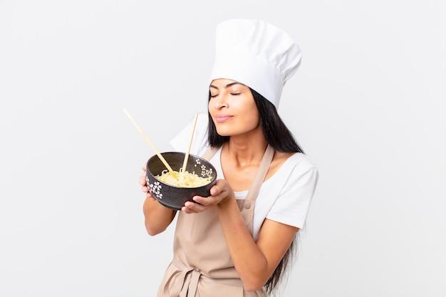 Hispanische hübsche kochfrau, die eine nudelschüssel hält