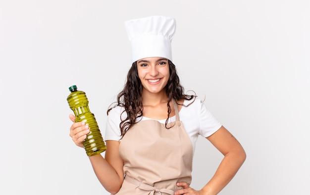 Hispanische hübsche kochfrau, die eine olivenölflasche hält