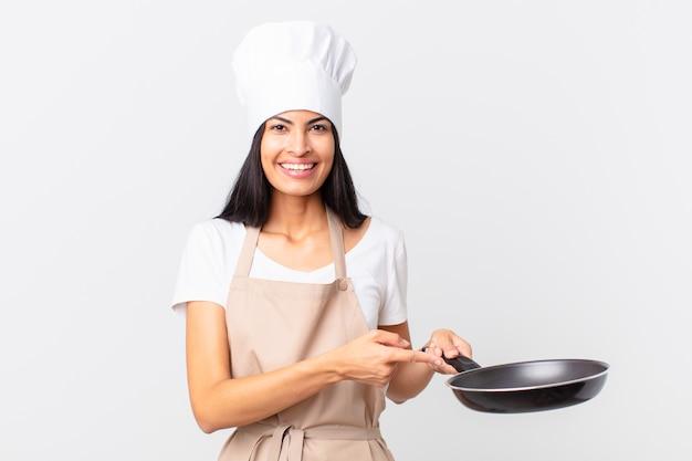 Hispanische hübsche kochfrau, die eine pfanne hält