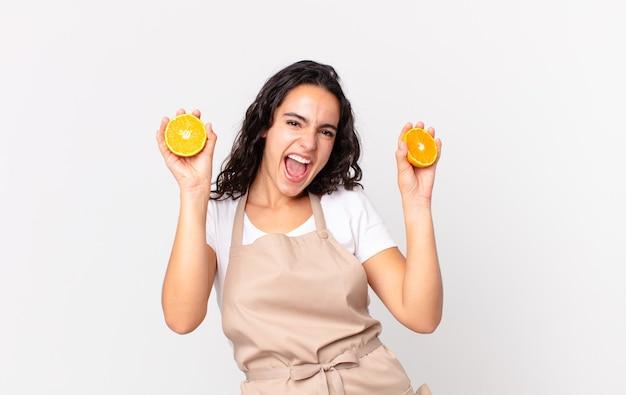 Hispanische hübsche kochfrau, die einen orangensaft zubereitet