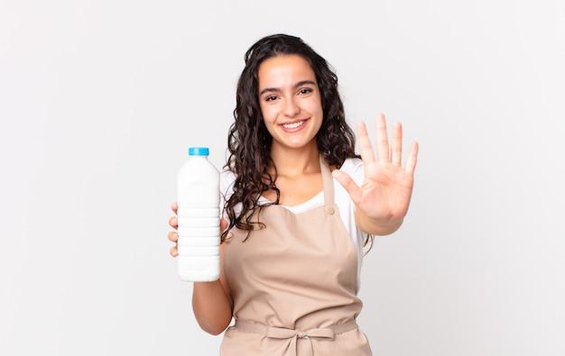 Hispanische hübsche kochfrau, die lächelt und freundlich aussieht, nummer fünf zeigt und eine milchflasche hält?