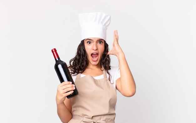 Hispanische hübsche kochfrau, die mit den händen in die luft schreit und eine weinflasche hält