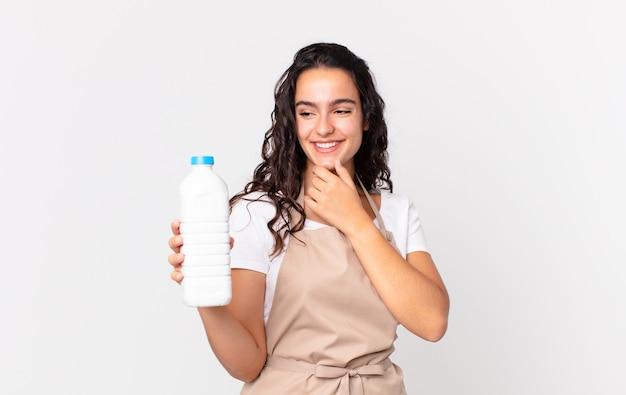 Hispanische hübsche kochfrau, die mit einem glücklichen, selbstbewussten ausdruck mit der hand am kinn lächelt und eine milchflasche hält