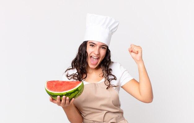 Hispanische hübsche kochfrau, die sich schockiert fühlt, lacht und erfolg feiert und eine wassermelone hält