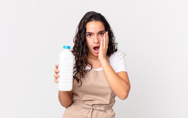Hispanische hübsche kochfrau, die sich schockiert und verängstigt fühlt und eine milchflasche hält