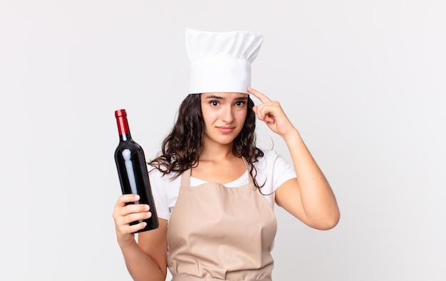 Hispanische hübsche kochfrau, die sich verwirrt und verwirrt fühlt, zeigt, dass sie verrückt sind und eine weinflasche hält
