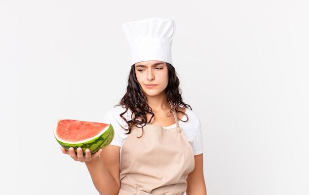 Hispanische hübsche kochfrau, die traurig, verärgert oder wütend ist und zur seite schaut und eine wassermelone hält