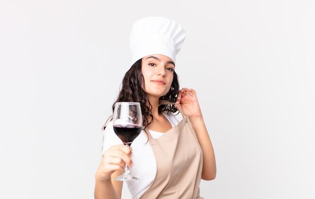 Hispanische hübsche kochfrau mit einem glas wein
