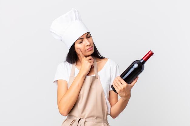 Hispanische hübsche kochfrau mit einer weinflasche