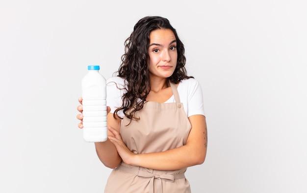 Hispanische hübsche kochfrau zuckt mit den schultern, fühlt sich verwirrt und unsicher und hält eine milchflasche