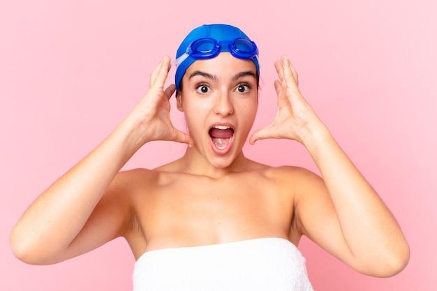 Hispanische hübsche schwimmerin schreit mit den händen in die luft mit brille
