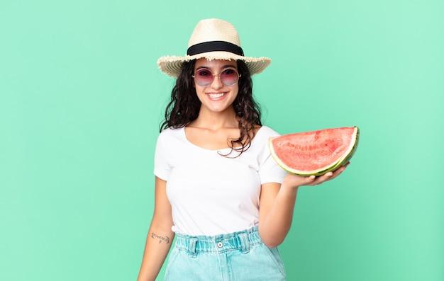 Hispanische hübsche touristenfrau, die eine wassermelone hält
