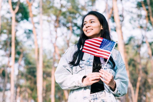 Hispanische jugendliche, die amerikanische flagge auf stock hält