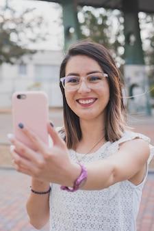 Hispanische junge frau, die mit ihrem telefon einen videoanruf tätigt